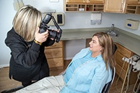Dental assistant using Digital Photography on patient do plan treatment