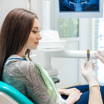 Woman at dentist office looking at dental implants