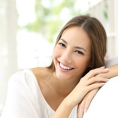 Smiling woman in white showing her teeth