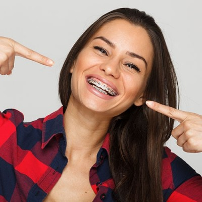 Woman smiling pointing toward her braces orthodontic treatment