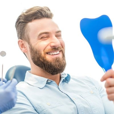 Man at dentist office looking a teeth in a mirror