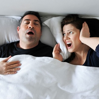 Woman covering her ears while her partner snores