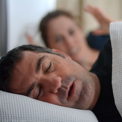 Man snoring with woman in background
