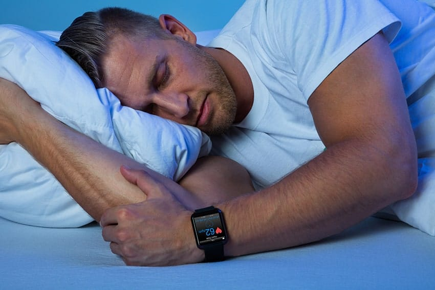 Handsome man sleeps in bed while his smartwatch monitors his apnea