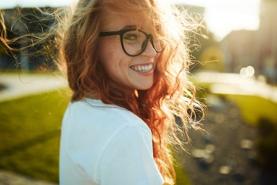 Woman with glasses in sun showing off her white fillings