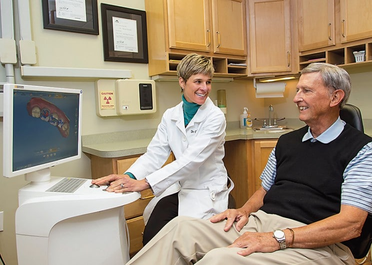 Dr. Grimshaw reviews image and discusses tooth replacement options with patient