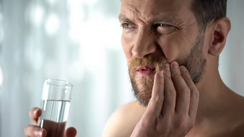 Man with tooth pain prepares to rinse his mouth