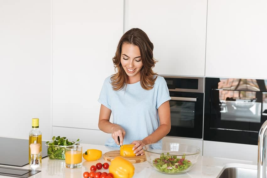 woman preparing a healthy salad at home