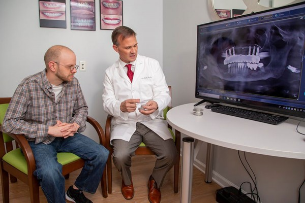 Dr. Kuhn and patient reviewing implant placement for All-on-4 dentures in Aberdeen