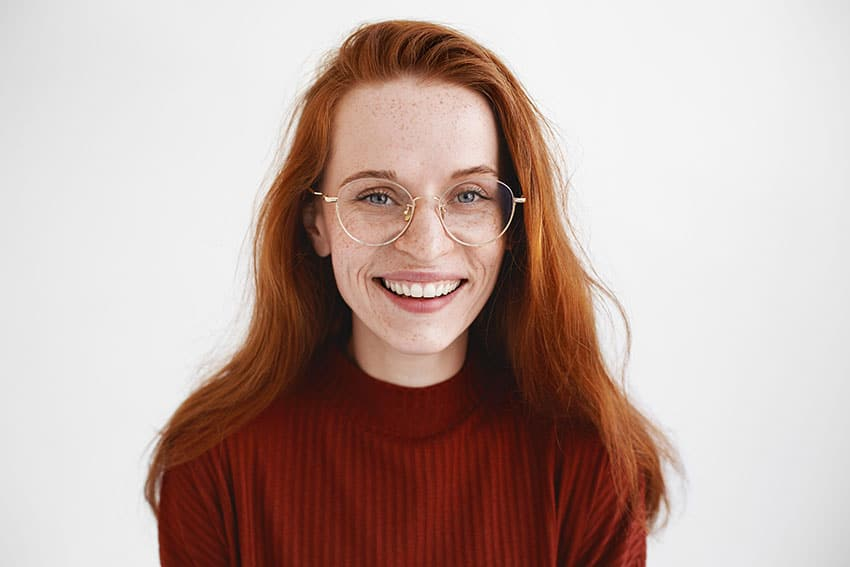 red head with large glasses shows off her smile