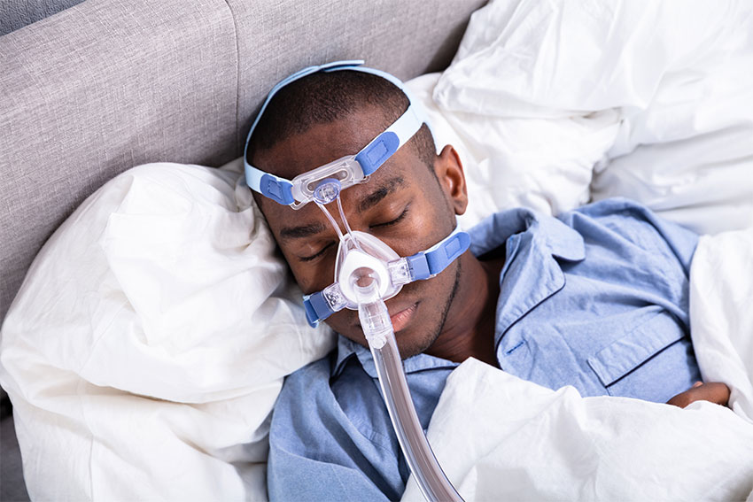 young man sleeping in bed with a large CPAP mask on his face