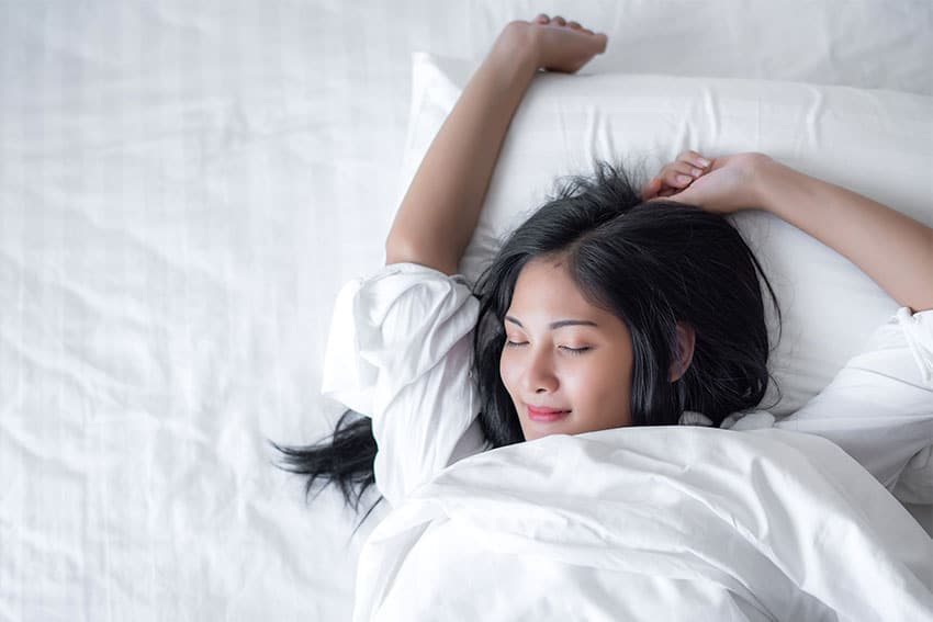 young woman waking up after a peaceful nights rest