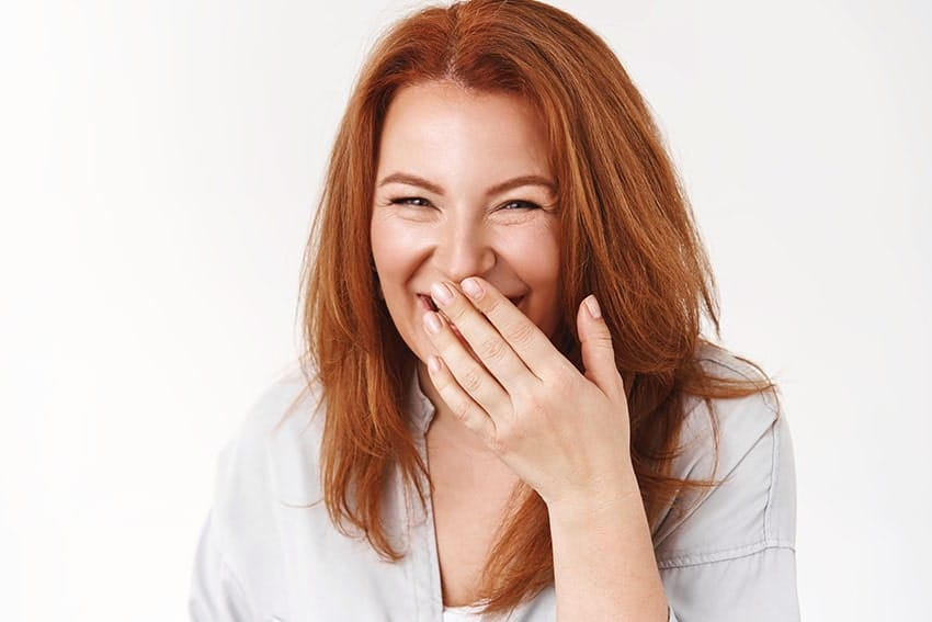 Woman covering mouth with bad breath