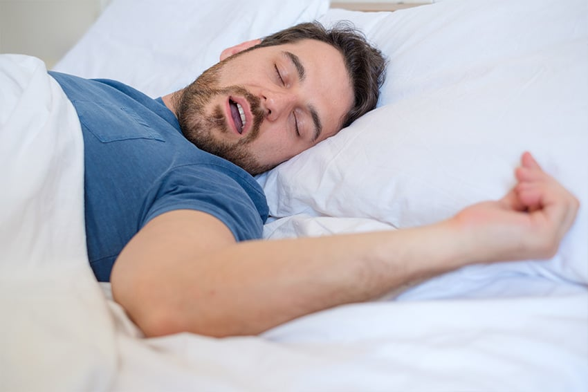 man snoring while laying on his back in bed