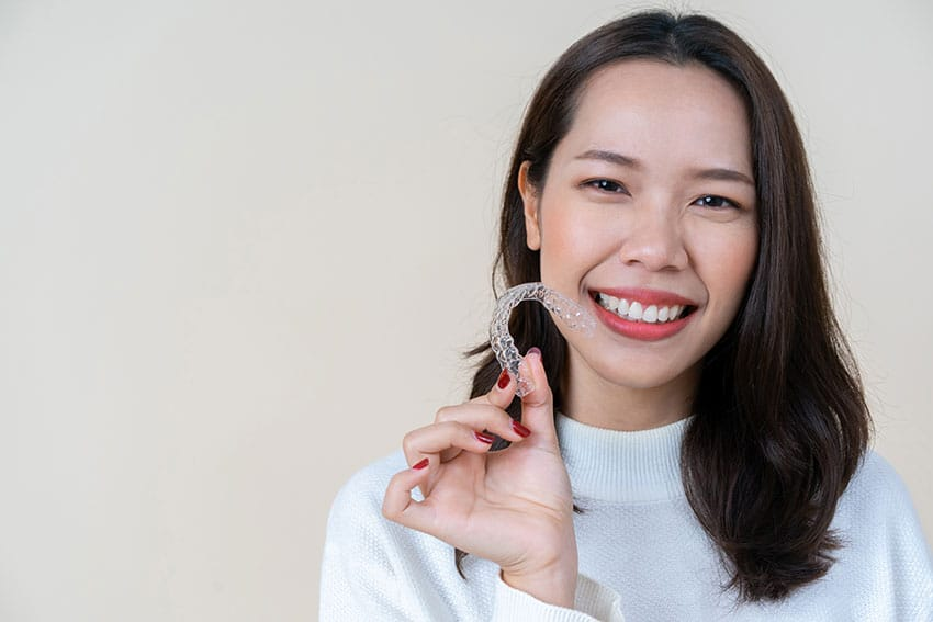 young woman showing off her Invisalign clear braces